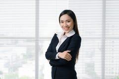 Уверенно азиатская коммерсантка стоя в современном офисе Стоковое Изображение RF