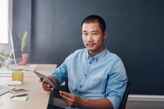 Уверенно азиатский дизайнер используя цифровую таблетку на работе Стоковые Фотографии RF