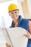 Уверенно архитектор держа светокопию на строительной площадке Стоковое Изображение RF