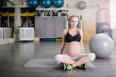 Уверенно беременная женщина сидя перекрестное шагающее Стоковые Фотографии RF