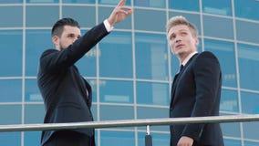 2 уверенно бизнесмена встречая outdoors на месте которое они идут обсудить акции видеоматериалы