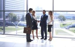2 уверенно бизнесмена тряся руки и усмехаясь пока стоящ на офисе вместе с группой в составе коллеги Стоковые Фото