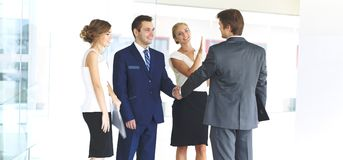2 уверенно бизнесмена тряся руки и усмехаясь пока стоящ на офисе вместе с группой в составе коллеги Стоковые Фотографии RF