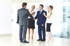 2 уверенно бизнесмена тряся руки и усмехаясь пока стоящ на офисе вместе с группой в составе коллеги Стоковое Изображение