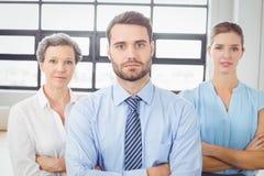 Уверенно бизнесмены при оружия пересеченные в офис Стоковая Фотография