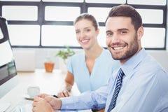 Уверенно бизнесмены сидя на столе компьютера Стоковые Фотографии RF