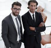Уверенно бизнесмены стоя совместно в офисе Стоковая Фотография RF