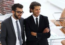 Уверенно бизнесмены стоя совместно в офисе Стоковое фото RF