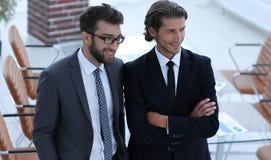 Уверенно бизнесмены стоя совместно в офисе Стоковые Изображения RF
