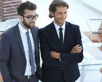 Уверенно бизнесмены стоя совместно в офисе Стоковая Фотография