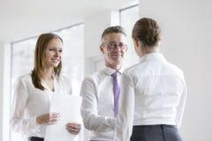 Уверенно бизнесмены тряся руки в офисе Стоковые Изображения RF