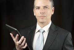 Уверенно бизнесмен держит таблетку Стоковая Фотография RF