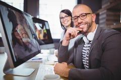 Уверенно бизнесмен компьютером с коллегой в предпосылке Стоковое Изображение