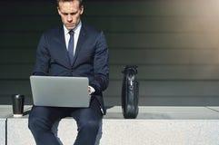 Уверенно бизнесмен пока работа с его компьтер-книжкой Стоковые Фото