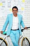Уверенно бизнесмен представляя с велосипедом стоковые фотографии rf