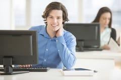 Уверенно бизнесмен сидя на столе офиса Стоковые Изображения RF