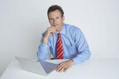 Уверенно бизнесмен сидя с компьтер-книжкой на столе стоковое изображение