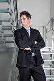 Уверенно бизнесмен стоя на лестницах стоковое изображение