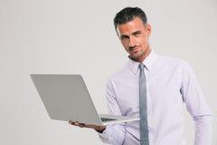 Уверенно бизнесмен стоя с портативным компьютером Стоковое Изображение RF