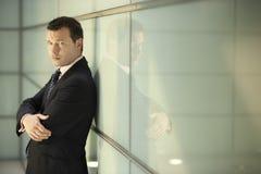 Уверенно бизнесмен с склонностью пересеченной оружиями на стеклянной стене Стоковая Фотография