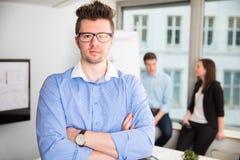 Уверенно бизнесмен с Eyeglasses пересеченными оружиями нося Стоковые Изображения RF