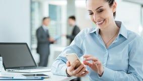 Уверенно бизнес-леди используя умный телефон Стоковые Фотографии RF
