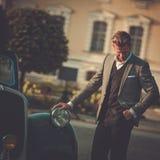 Уверенно богатый человек около классического автомобиля с откидным верхом стоковое фото rf