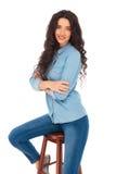 Уверенно вскользь женщина сидя с пересеченными руками и улыбками Стоковая Фотография RF