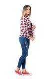 Уверенно вскользь женщина стиля улицы представляя держащ воротник рубашки шотландки Стоковая Фотография RF