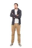Уверенно вскользь человек при пересеченные оружия смотря вверх нося серый свитер застежка-молнии стоковые фото