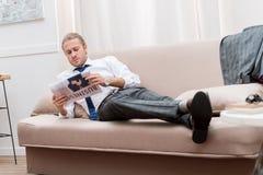 уверенно газета чтения бизнесмена пока отдыхающ на софе Стоковое Фото