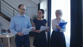 Уверенно деловые партнеры идя вниз в офисное здание и обсуждая работу Стоковые Изображения RF