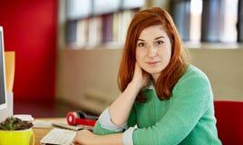Уверенно женский дизайнер работая на ее столе в красных творческих размерах офиса Стоковые Изображения RF