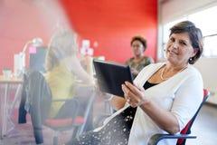 Уверенно женский дизайнер работая на цифровой таблетке в красных творческих размерах офиса Стоковые Фото