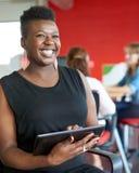 Уверенно женский дизайнер работая на цифровой таблетке в красных творческих размерах офиса Стоковое фото RF