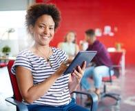Уверенно женский дизайнер работая на цифровой таблетке в красных творческих размерах офиса Стоковые Фотографии RF