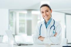 Уверенно женский доктор на столе офиса стоковые фото