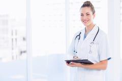 Уверенно женский доктор с доской сзажимом для бумаги в больнице Стоковая Фотография