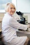 Уверенно женский ученый используя микроскоп в лаборатории Стоковые Фото