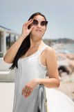 Уверенно женщина на солнечной предпосылке пляжа Дама на летних каникулах Женщина в сером платье и броский стоковые изображения