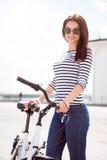 Уверенно женщина стоя около велосипеда Стоковое Фото