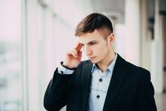 Уверенно заботливый бизнесмен в костюме держа руку на подбородке и смотря отсутствующий пока стоящ с офисным зданием в backgr Стоковое Изображение RF