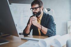 Уверенно задумчивый архитектор в официально носке думая и работая с планами настольного компьютера и чертежей в современном Стоковое Фото