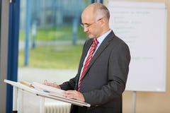 Уверенно зрелое чтение бизнесмена на подиуме Стоковое Изображение RF