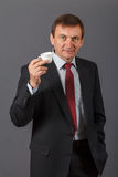 Уверенно зрелый бизнесмен стоя перед серым backgro Стоковые Изображения RF