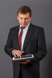 Уверенно зрелый бизнесмен стоя перед серым backgro Стоковое Изображение RF