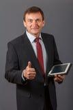 Уверенно зрелый бизнесмен стоя перед серым backgro Стоковое фото RF