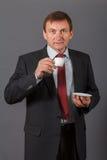 Уверенно зрелый бизнесмен стоя перед серым backgro Стоковые Изображения