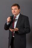 Уверенно зрелый бизнесмен стоя перед серым backgro Стоковые Фото