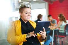 Уверенно и нервный женский дизайнер работая на цифровой таблетке в красных творческих размерах офиса Стоковое Изображение